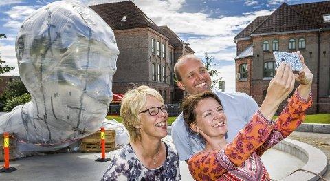 Selfie: Unni Skaar, Guro Elise Berg og Sindre Martinsen-Evje inviterer til folkefest når kong Harald kommer til Sarpsborg fredag 29. juli. Her tar de selfie foran «Genesis» som kongen skal avduke.