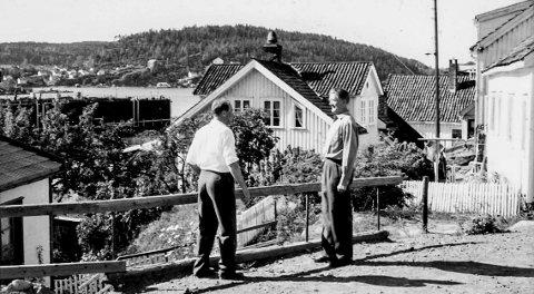 Smedsbukta rundt 1975: Vi er noe usikre på årstallet, men her møtes to personer som var meget kjente i Kragerø tidligere. Kjøpmann Gunnar Thorsdal (t.v.) og brannmester Sverre Muffetangen. Fotografiet er tatt like ved Thorsdals kolonialbutikk. I bakgrunnen ligger den gamle flytedokka som tilhørte Kragerø Slipp & Mekaniske Verksted. Legg merke til at veien er uten asfalt.