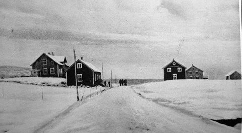 Øverst til venstre sees den gamle amtskolen som senere ble flyttet til Fauske. Til venstre den røde butikken til Kristian Jakobsen. På veien ser vi hest og folk. På høyre side av veien ses det røde våningshuset til Kristian Jakobsen. Bak dette ses huset til Johan Larsen. Der bodde Henrik Mortensen som senere overtok huset. Helt til høyre er fjøset til Johan Larsen.