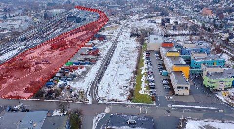 Det er på området mellom den røde skraveringen og veien midt i bildet Bane NOR Eiendom vil bygge rundt 250 nye boliger. Den røde skraveringen viser den planlagte togparkeringen, og til høyre ligger Gulskogen skole.
