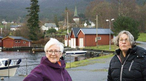MIDT I BYGDA: Signe Alice Birkeland (til venstre) og Ingrid Mathilde Sørvåg på «prestakaien» med sentrale deler av Midtbygda i Vikebygd i bakgrunnen. Denne hausten opplever bygda eit sjeldent bokslepp: To bygdebøker og ei tur- og bildebok som alt er utseld.  8Foto: Sebastian Laksfoss Cardozo