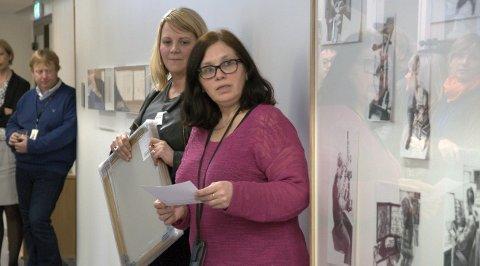 Leder for Kartverkets kunstforening Irmelin Kårbø (i rosa) forteller om verkenes betydning for Kartverket, kurator for KORO Merete Røstad bak i sort.