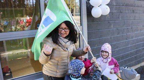 GRØNT FLAGG: Barna hjelper mer enn gjerne Irene Brevad fra Vestby kommune til å få på plass det grønne flagget på Grevlingen barnehage. (Foto: Mattias Mellquist)