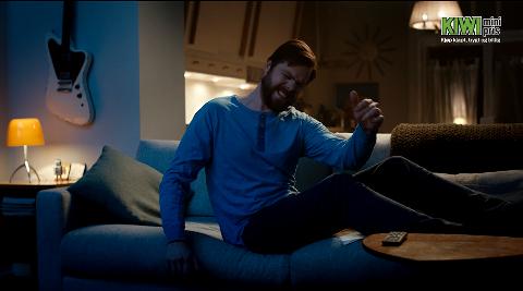 I SAMME SERIE: Kiwi har også en lignende reklame med en mann. I stedet for å strekke seg ned mot gulvet, strekker han seg mot fjernkontrollen – og tar seg et par magebøyninger i samme slengen.