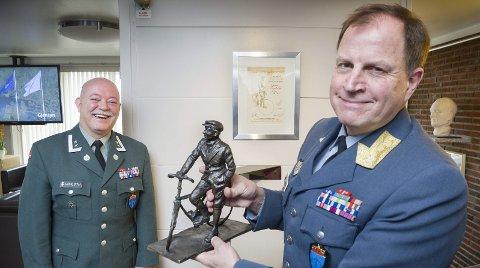 HEDERSPLASS: Veteraninspektør Tom Guttormsen med statuetten av «Kjakan» ved sykkelen. Sjefen for Veteransenteret, Johnny Sørloth smiler fornøyd.