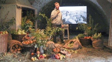 MIDT I FRUKTFATET: Per Christian Brown poserer med et eple i kjeften, midt inni sin egen installasjon i en av kasemattene.