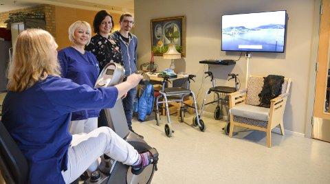 TV: Annlaug Mannsåker demonstrerer sykkelen for Jelena Birkeland, Birthe Kvile Nes og Tommy Rønnåbakk som kom frå IKT for å installera TV-skjermen.