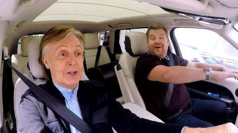 """Paul McCartney overtar et kort øyeblikk karaokebil-rattet fra programleder James Corden, mens de synger """"Baby You Can Drive My Car""""-refrenget fra Beatles-låten. Skjermdump: James Corden Carpool Karaoke"""