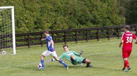 LÆREBOKA: Så lett gjør en målscorer det. Målet er tatt ut av læreboka når Eirik Høgseth finter ut Grand-keeperen og scorer sitt mål første mål.  FOTO: PER VIKAN