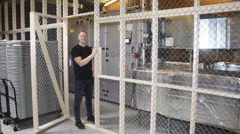 HJERTET: Kjetil Hoff står i døra til hjertet av det nye varme- og ventilasjonsanlegget i Mosjøhallen. Her styres friskluft og omluft og sendes ut i hallen. Foto: Per Vikan
