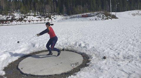 BAR BAKKE: Guro Martine Brøndbo Dahl i kastringen på skistadion. Hun trener hardt for å kvalfisere seg til junior-NM i slegge. Det har foregått dugnad på alle banene, og utøverne har fått muligheter til å trene ute. Foto: Privat