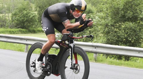 LINDESNES - NORDKAPP: Øystein Dahl (47) sykler Norge på langs i et verdensrekordforsøk. Han startet fra Lindesnes torsdag morgen og passerte Mosjøen midt på dagen lørdag. Her hilder han til fotografen på Alsgården i Bjørnådalen. Han har stort sett brukt temposykkelen, men har også noen mil på landeveissykkelen.  Foto: Per VIkan