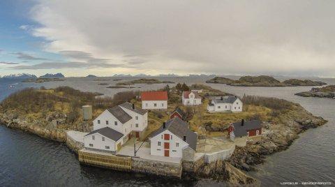 Vakthusøy: I dag ligger Vakthusøy slik i utkanten av det koselige fiskeværet Henningsvær i Lofoten, med Vestfjorden mot øst i bakgrunnen. Dronefoto: LOFOKUS Eiendomsfoto