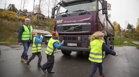 VINK TIL EN VENN: – Husk og se etter sjåføren og vink til han. Når han vinker tilbake kan dere gå over veien, sier Olav Kortnes, og ungene løper ivrig foran den store bilen.