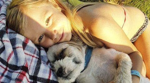 Kveldskos: Alexandra (8) og hunden Andy nyter sommerkvelden sammen. Foto: Else Charlotte Holmstad