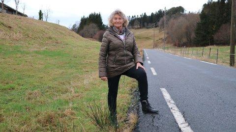 Her står Sissel-Anny Hjelmtveit ved Fv. 401 på Seimstranda på Seim for å vise kor høg vegkanten er.