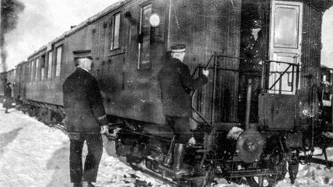 Kragerø Jernbanestasjon 1930: Toget til Oslo står klar til avgang på Kragerø jernbanestasjon. Røyken fra damplokomotivet stiger opp. Det er vinter og skyggene forteller oss at det er ettermiddagstoget som står på stasjonen. Den gang var Kragerø fortsatt endestasjon for Sørlandsbanen. Kragerøbanen, fra Neslandsvatn ble åpnet i desember 1927 og lagt ned 60 år senere.