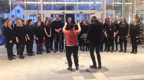 SUPERDIRIGENTEN: Dirigent Chris Johnson lot gladelig Vetle Bonesvoll overta korledelsen da Beat opptrådte på Hvaltorvet. (Foto: Screenshot fra videoen).