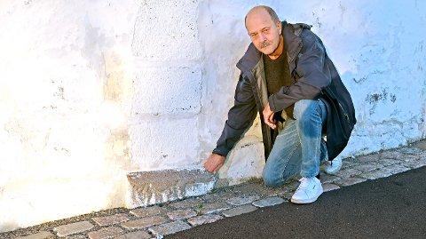 ÅSTEDET: Arkeolog Jan Brendalsmo viser hvordan en del av kirkens sørportal er tildekket. Det er ikke lenger mulig å se det nederste partiet med figurene fra tidlig 1100-tall.