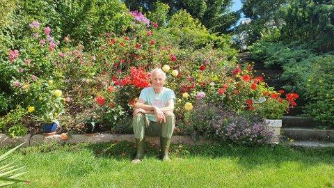 Her sitter Oddvar Bjerke foran en av mange deler av hagen som har roser.