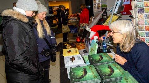 PÅ SHOPPING: Hedda Hvamstad Skuterud (12) (nærmest) og Selma Elind (12) tar en titt på naturbøkene til Synnøve Borge. De syntes tegningene ved første øyekast virket litt barnslige. Forfatteren sa de var akkurat i overkant aldersmessig for bøkene. Tegningene er forøvrig illustrert av Lise Myhre, som også tenger Nemi.