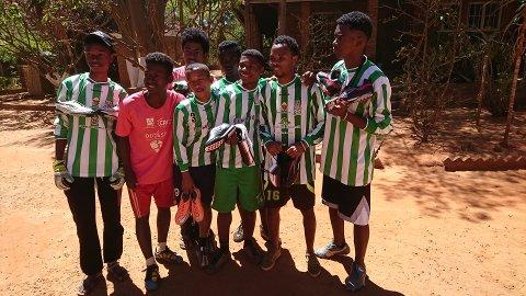 Glade ungdomar med nye fotballsko og drakter til laget.