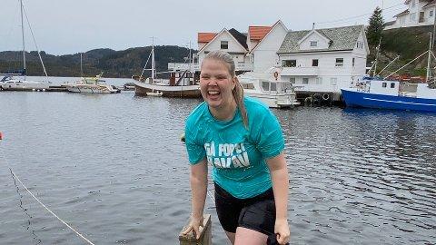 Ein klissvåt Sara Hamre Sekkingstad på veg opp av vatnet etter å ha blitt dytta uti av Thomas Larsen.