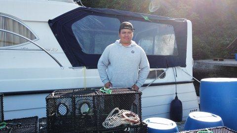Eirik Haugland (17) er blant ungdommane som har jobba som fiskar i sommar. Her fiskar han til teinene sine på kaia.