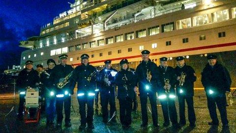 Ikke helt enkelt å få øye på musikerne i Bergen Brandkorps Musikkorps på Bontelabo, men konsert ble det til glede for turistene om bord på «Black Watch» i bakgrunnen. (Foto: PRIVAT)