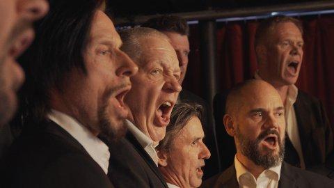 Lørdag tar Mannskoret, kjent fra filmen «For vi er gutta» oppstilling på Ole Bull Scene. Det er andre gang de synger i Bergen. Første gang var på en lekter på Vågen. FOTO: Filmweb