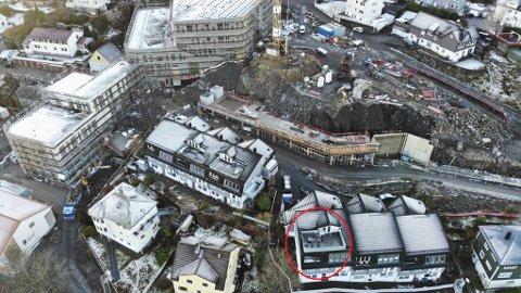 Familiens hus er fanget mellom ulike byggeprosjekter. Bak og på siden pågår Holen skole-utbyggingen. På fremsiden, utenfor bildet, pågår også veiarbeid, rørutskifting, trafokioskbygging og tilrettelegging for trolleybussene.