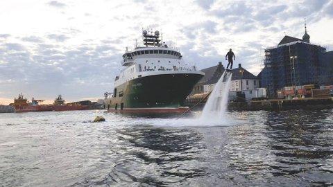 Mange tok frem mobilkameraet da de oppdaget Stian Midlang som svevde på flyboard mellom båtene i Vågen lørdag kveld. Håkonshallen og Bergenhus festning i bakgrunnen.