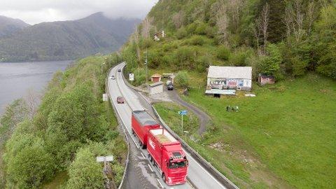 Næringslivet reagerer på utsettelsen av nye E16. I bakgrunnen kan du se skiltet Norges miljøvernforbund har hengt opp på en låve ved Trengereid.