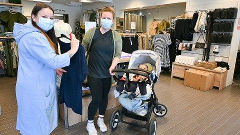 FORTSATT MUNNBIND: Både butikkeier Kjersti Eriksen (t.v.) og kunde Anja Holm Finsrud kommer til å fortsette å bruke munnbind inntil videre. Halvannet år gamle Theo i vogna trenger derimot ikke tenke på munnbind.