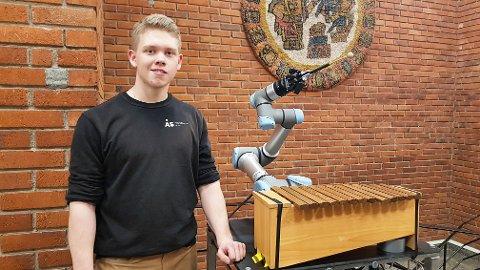 """Didrik Esbjug ved en moderne universalrobot som i anledning kåring av Årets elev var programmert til å spille """"Lisa gikk til skolen"""" på xylofon."""