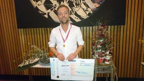 FYRSTEPLASS: Sindre Ellila (34) vann gull i si klasse i blomsterdekoratørfaget. Hovudoppgåva kan ein skimte bak til høgre for vinnaren.
