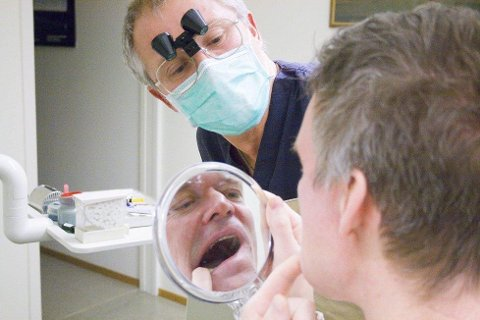 SJEKKER: Robert Larsen tar første titt på sin nye krone. Tannlege Thorbjørn Berger venter spent på reaksjonen.