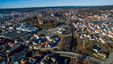 Det er full enighet om at byens nye jernbanestasjon skal ligge i sentrum. Den utpekte tomten ligger på Grønli, mellom Glemmen kirke og Glemmen videregående skole. På bildet ser vi Dammyr-brua foran, kirken til venstre og skolen til høyre.