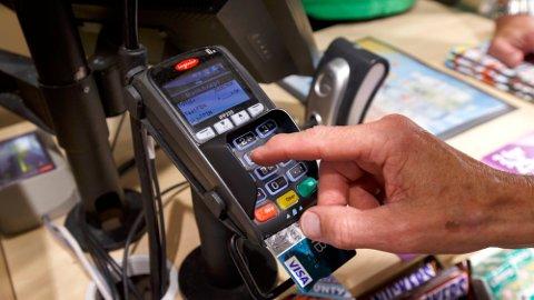 BETALING: Ørland sparebank er en av bankene som tar seg betalt for at kundene foretar varekjøp. Foto: Heiko Junge (NTB)