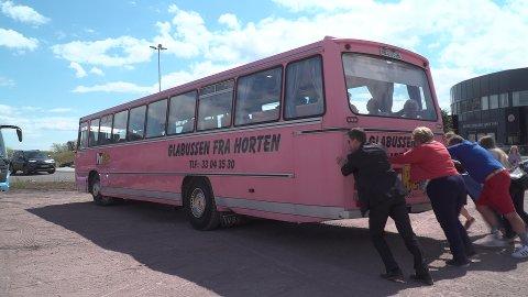MÅTTE DYTTE: Erna Solberg var den første til å melde seg, og fikk hjelp av flere andre med å dytte bussen i gang.