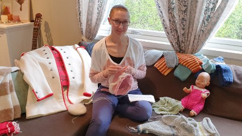 Chanita Thue Fagerhaug er med å stifte Øyer husflidslag. Dokka i sofaen har på seg plagget som gjorde at hun ble bitt av strikkebasillen. Bunaden er også Chanitas verk.