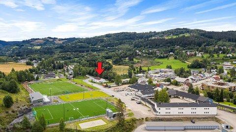 SENTRAL BELIGGENHET: Bedehuset som er solgt er markert med rød pil, og ligger sentralt til på Roa. Frøystad-anlegget er i forgrunnen på bildet.