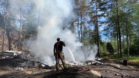 Brannvesenet med etterslukking i brannruinene.