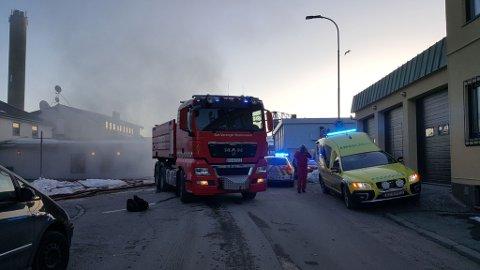 RØYKUVIKLING: Det har lagt seg mye røyk i Kirkenes sentrum. Nødetatene jobber på stedet.