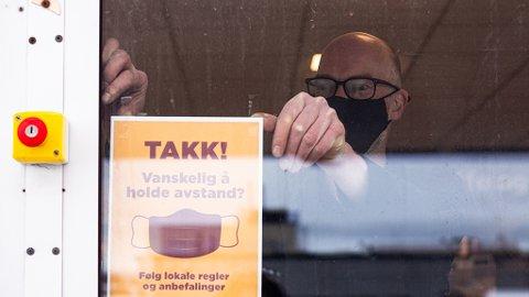 HENGER OPP PLAKATER: Daglig leder ved Circle K Vadsø, Raymond Ananiassen henger opp plakater med informasjon om bruk av munnbind.