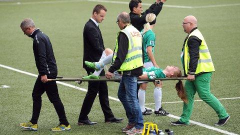 Katrin Asbjørnsdottir bæres av banen med trener Jon Pall Palmason som bekymret tilskuer. Anette Tengesdal gjør seg klar til å komme inn.
