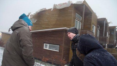 TATT AV VINDEN: Det blåste fremdeles friskt fredag formiddag da beboerne Kristian       Knudsen (til venstre), Odd Tunheim og Ingvild Egeland (med ryggen til) var ute for å se på skadene på boligene sine fredag formiddag. Nå tar utbyggeren på seg ansvaret.