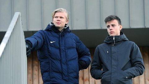 Erling Braut Håland (t.v.) var tilskuer da Bryne spilte mot Sandnes Ulf lørdag. Her ser han andre omgang sammen med Adrian Berntsen, som startet kampen for Bryne. De to har vært lagkamerater i mange år på aldersbestemte Bryne-lag, men nå skilles deres veger.