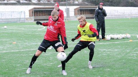 Bjarne Langeland (t.v.) i duell med Frank Hole på en trening på Rosselandbanen. I bakgrunnen følger Erik Rosland og trener Ole Hjelmhaug nøye med. Dette var før det ble virkelig kaldt.