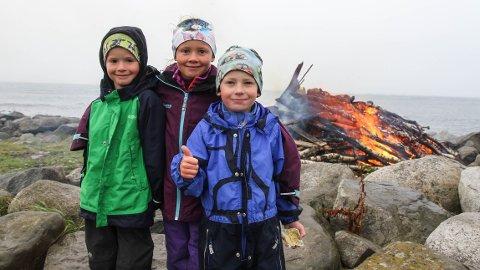 Tore Laugen (6), Tomine Bjorland (7) og Mandius Bjorland (5) synes det var godt å få varmet seg etter å ha vært ute i regnet lenge.